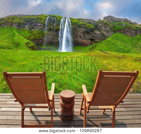 The warm July day in Iceland. Seljalandsfoss waterfall. Deck chairs on the wooden floor waiting for tourists