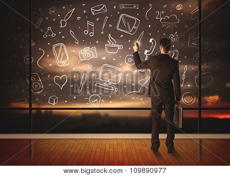 Businessman drawing media icons on glass window, bokeh cityscape background