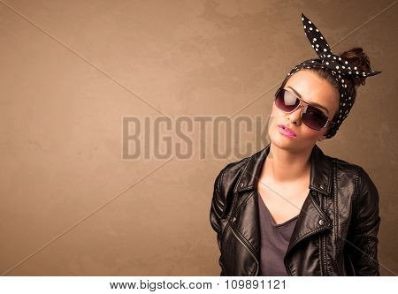 Portrait of a young pretty woman with sunglasses and copyspace on brown background