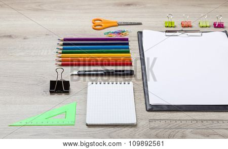 school supplies with pencils, paint pens paper scissors and rulers.