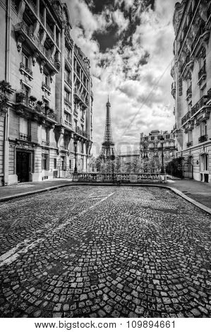Eiffel Tower seen from the street in Paris, France. Black and white. Free space on cobblestone pavement for your object, text etc.