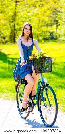 Young woman in short colorful dress with long hair rides a bicycle with basket and flowers tour summer city park, look and smile to camera