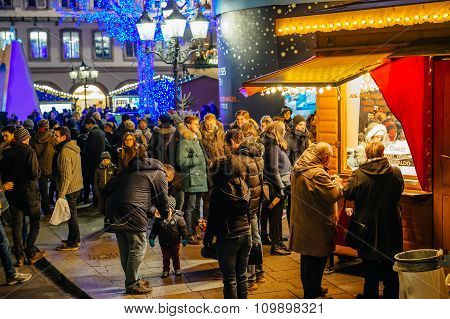 People Buying Food At Christmas Market Stall
