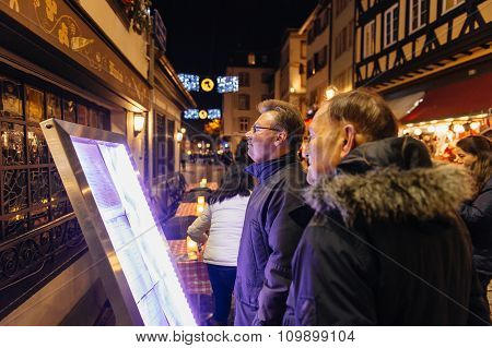 People Reading Christmas Menu In Front Of The Restaurant