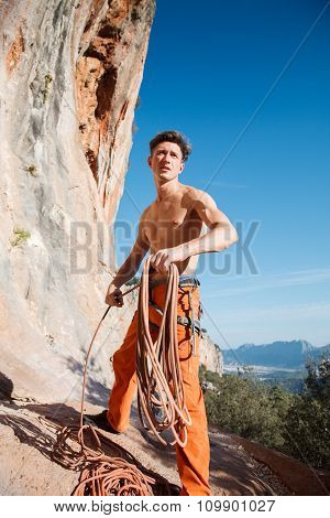 Rock Climber Collecting The Rope