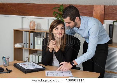 Young Man And Woman Working Together In Office,