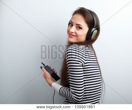 Happy Beautiful Woman Holding Player And Listening Music In Headphones On Blue Background