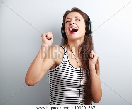 Dancing Happy Active Young Woman In Headphones Singing The Song On Blue Background