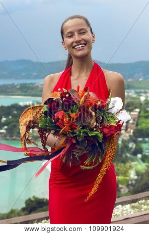 Fashion woman in red dress with flowers posing on tropical sea view. New year ball. Phuket island, T