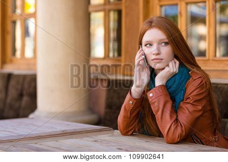 Beautiful pensive redhead young woman in leather jacket  talking on cell phone in outdoor cafe