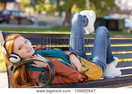 Joyful smiling redhead girl in leather jacket, jeans and white boots relaxing on the bench in the park and listening to music using headphones