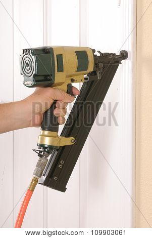 Carpenter using an angle nail gun to complete door framing trim