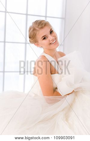 Portrait of a happy bride standing in white wedding dress and looking at camera