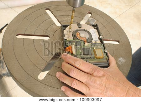 Worker destroying data by drilling through the hard drive with an upright free standing power drill