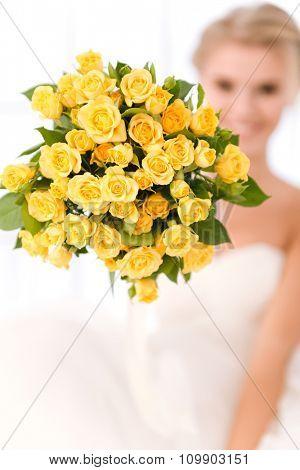 Closeup portrait of a bride holding flowers. Focus on flowers