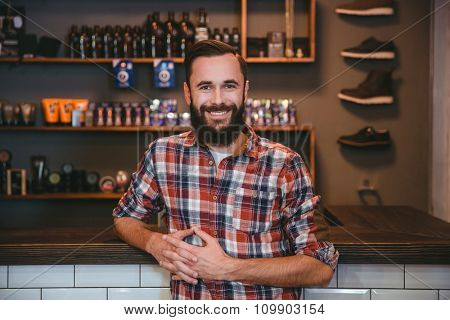 Joyful smiling content  bearded man in checkered shirt posing in barbershop