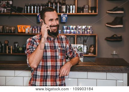Positive smiling bearded man in checkered shirt talking on mobile phone in barbershop