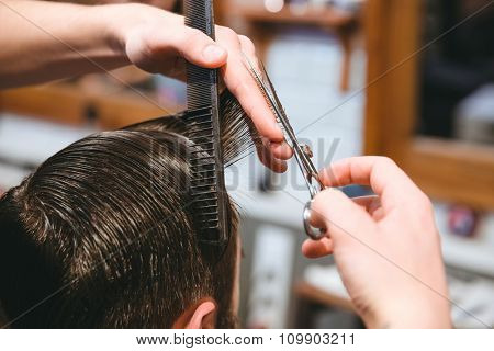 Closeup of barbers hands making short haircut to man using comb and scissors in barbershop