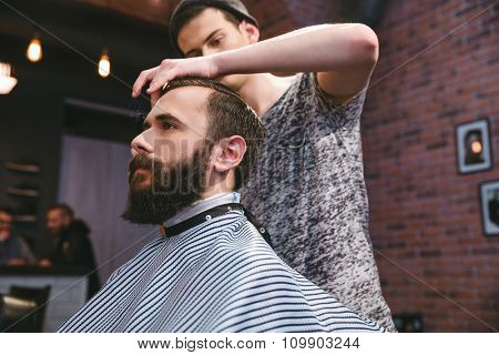 Young handsome barber cutting hair of young attractive bearded hipster in barbershop