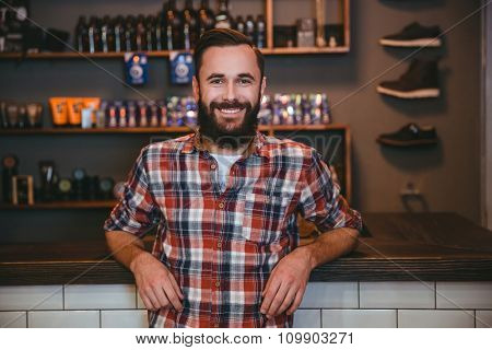 Happy cheerful satisfied man with beard in plaid shirt in barbershop after visiting barber