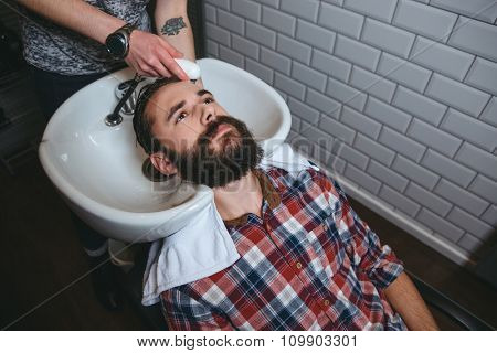Hairdresser washing hair of young attractive man with beard in checkered shirt in hairdressing salon