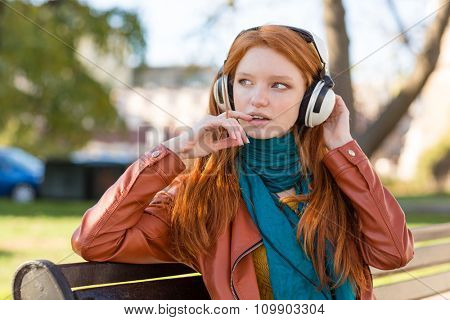 Pretty cute young redhead woman in leather jacket listening to music using headphones on bench in park