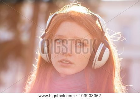 Closeup of thoughtful pretty young lady with long hair in headphones