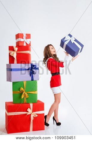 Full length portrait of attractive excited young woman in red santa claus dress throwing up present box isolated over white background