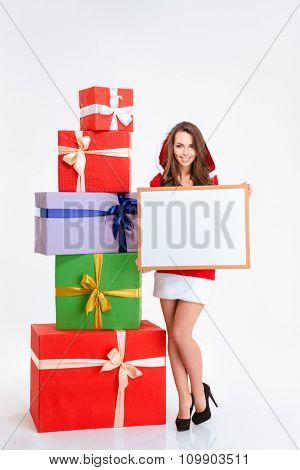Full length portrait of a smiling woman in santa claus cloth holding blank board isolated on a white background