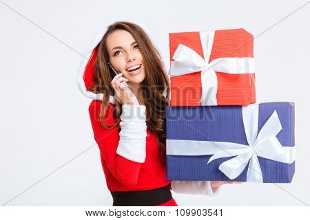 Cheerful attractive young lady in red santa claus costume with hood holding presents and talking on mobile phone isolated over white background