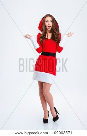 Full length portrait of amazed confused curly girl in red costume of santa claus with hood pointing both ways over white background