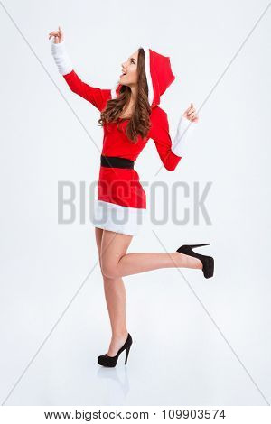 Happy content curly young woman in red santa's clothes with hood with hands like taking something from the top isolated over white background