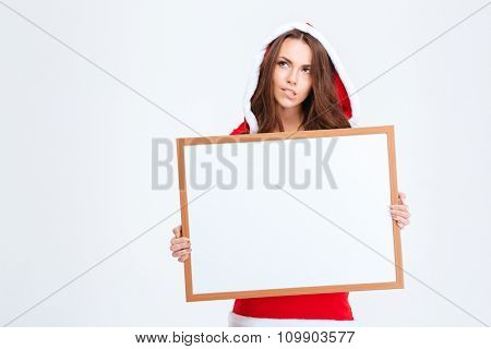 Thoughtful pretty young woman in santa claus dress with hood biting bottom lip and holding blank board over white background