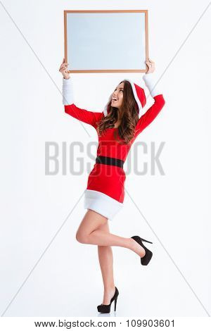 Full length portrait of a cheerful woman in santa claus cloth holding blank board over head isolated on a white background