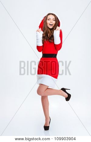Full length portrait of happy excited beautiful young curly female in red costume of santa claus with hood posing over white background
