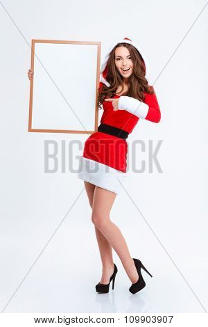 Full length portrait of charming attactive cheerful curly young woman in santa claus dress with hood pointing on blank board and holding it over white background