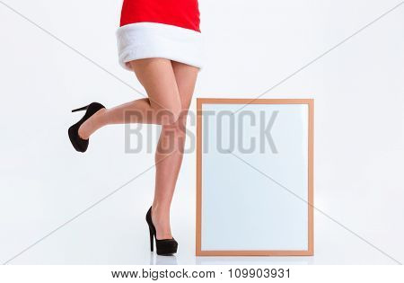 Closeup portrait of a female legs in santa claus cloth and blank board isolated on a white background