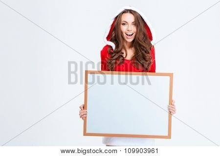 Portrait of a cheerful woman in santa claus cloth holding blank board isolated on a white background