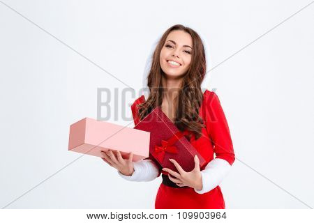 Cheerful pleased charming young woman in red santa claus costume with hood holding opened present on white background