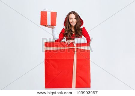 Attractive excited cheerful curly young woman in red santa claus costume with hood sitting inside the gift box and holding red present box with white ribbon over white background
