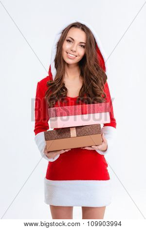 Beautiful smiling happy young female in red santa claus costume with hood standing with two gifts over white background