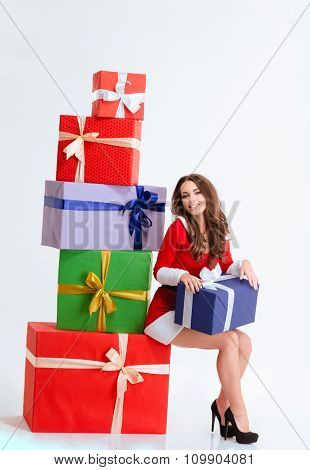 Charming cheerful young female in red santa claus dress  sitting on the colorful gift boxes isolated over white background