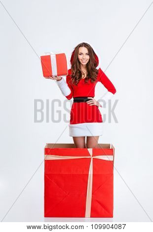 Attractive cheerful curly young lady in red santa claus costume with hood jumping out of present box holding red gift box over white background