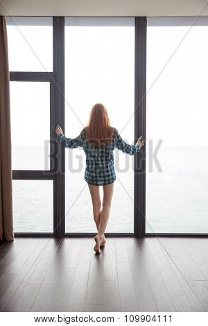 Back view of sensual attractive young lady with beautiful long red hair in checkered shirt standing barefoot in front of the big window