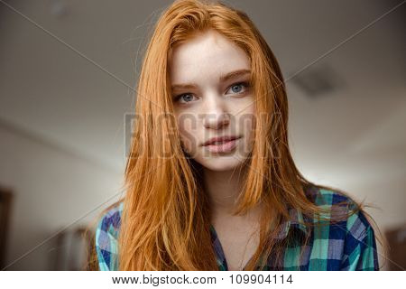 Portrait of thoughtful attractive redhead young woman in plaid shirt looking camera
