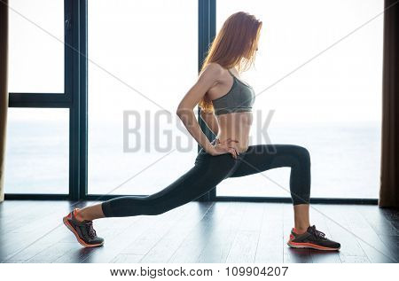 Portrait of a redhead fitness woman doing warm up exercises