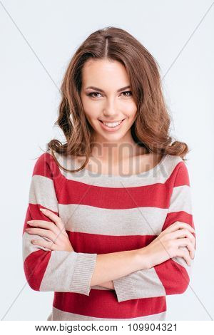 Portrait of a happy cute woman standing with arms folded isolated on a white background and looking at camera