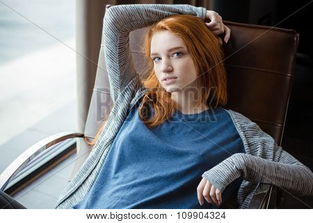 Portrait of a beautiful redhead woman relaxing on rocking chair at home