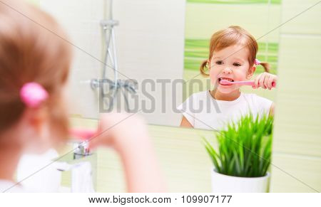 Happy Child Girl Brushing Her Teeth Toothbrushes In Bathroom