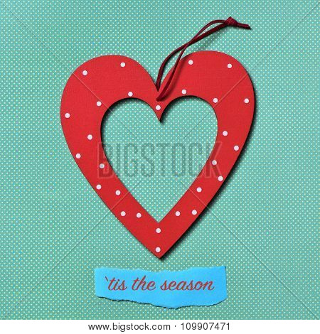 a red heart-shaped christmas ornament and the text tis the season on a colorful blue dot patterned background